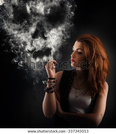Girl smokes a cigarette forming a skull - stock photo