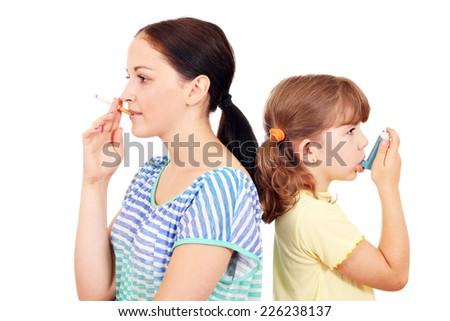 girl smoking cigarette and little girl use inhaler - stock photo