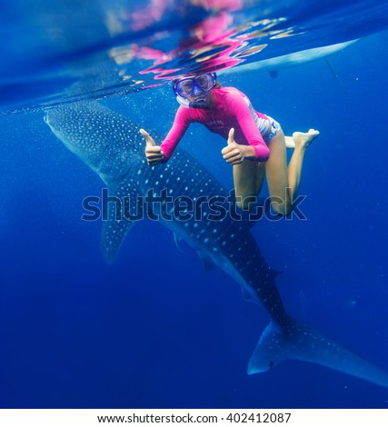 Girl snorkeling with whale shark - stock photo