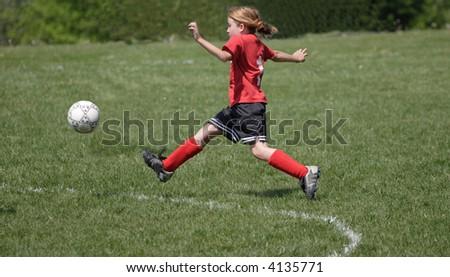 Girl Soccer Player Kicking Ball - stock photo