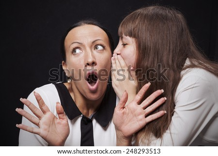 Girl speaks ear of a young surprised woman on a black background - stock photo