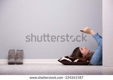 girl spending some time in relax lying down on the floor with her tablet - stock photo