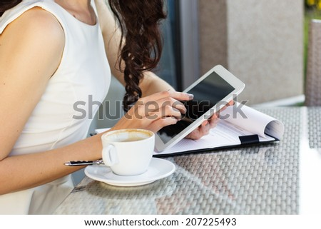 Girl spending time in a cafe using digital tablet - stock photo