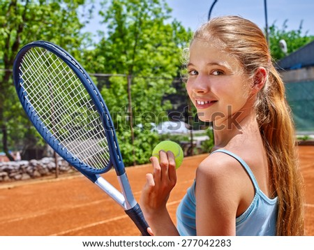 Girl sportsman with racket and ball on  tennis court. Green tree ang blue sky on background. Looks over her shoulder - stock photo