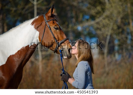 Girl sportswoman and her horse after a riding in the spring - stock photo