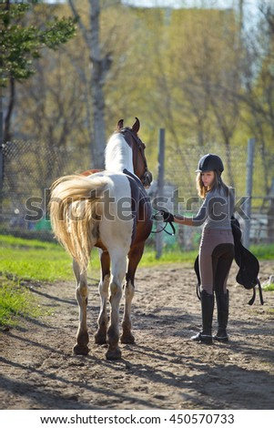 Girl sportswoman and her horse back to the stables after riding - stock photo