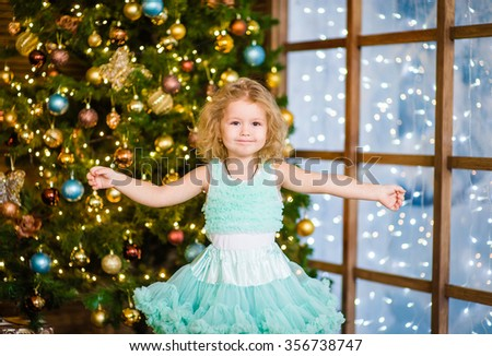 Girl spread her arms to the side near the Christmas tree - stock photo