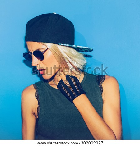 Girl standing at blue Wall in stylish Glasses and Cap. Urban style - stock photo
