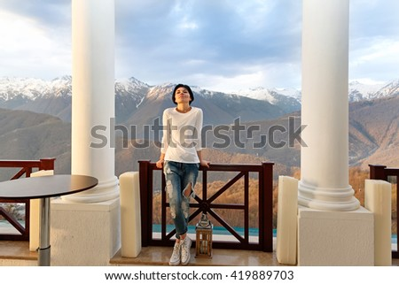 Girl standing at the railing at sunset with mountains in the background - stock photo