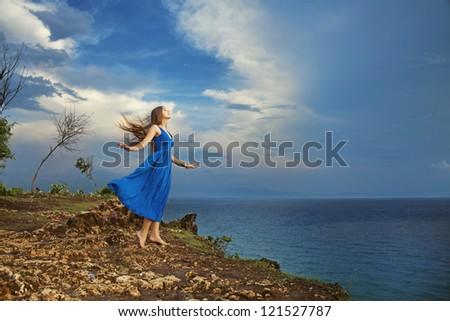 girl standing high against ocean, bali - stock photo