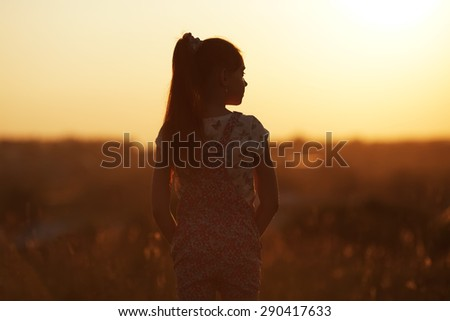 Girl standing in a field and looks into the distance - stock photo