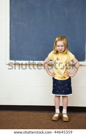 Girl standing in school classroom with hands on hips and pouty facial expression. Vertically framed shot. - stock photo