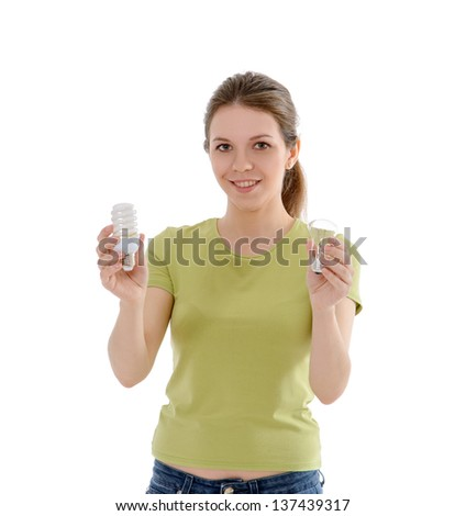 Girl standing isolated on white background holding energy saving bulb and usual light bulb, metaphor for energy saving - stock photo