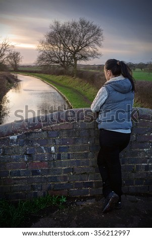 Girl standing on a canal bridge looking at sunset reflected in the water - stock photo