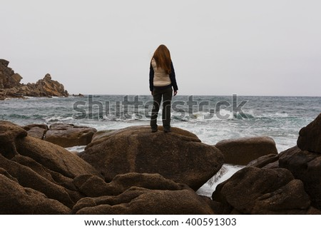 girl standing on a rock by the sea - stock photo
