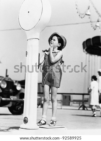 Girl standing on a weighing scale - stock photo