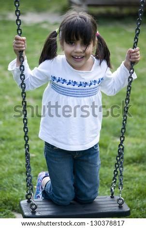 Girl standing on swing - stock photo