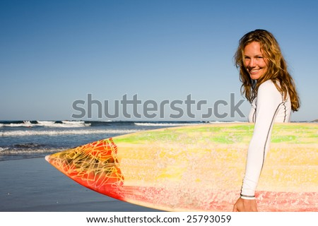 Girl standing on the beach holding a surfboard - stock photo