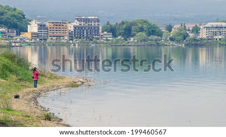 Girl standing on the lake shore with city view - stock photo