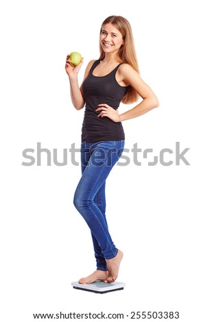 Girl standing on weight scale with an apple - stock photo