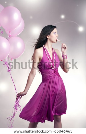 Girl standing with balloons and lollipop - stock photo