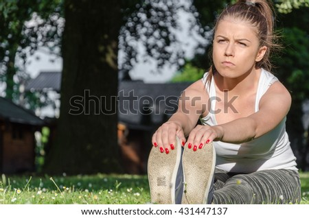 girl stretches the muscles and ligaments in nature - stock photo