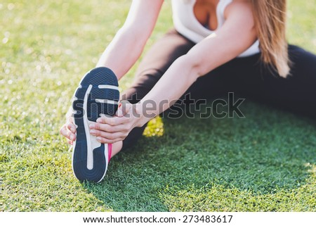 Girl stretching her foot on a grass on stadium field. Warming up before training. No face - stock photo
