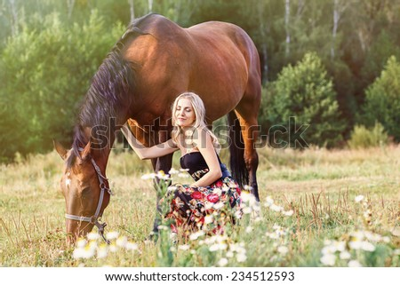 Girl stroking horse in field. beautiful girl near a horse on the meadow with daisies - stock photo
