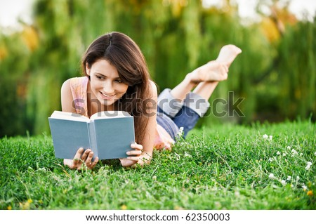 Girl-student lies on lawn and reads textbook. - stock photo