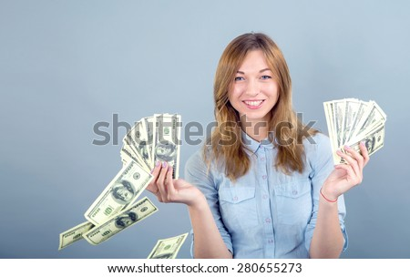 Girl student or young business woman holds the money, one hundred dollar bills US. Throw money. The concept overspend. Money down the drain. Money flying out of the hands of women. Blue background. - stock photo