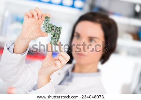 girl student studying electronic device with a microprocessor - stock photo