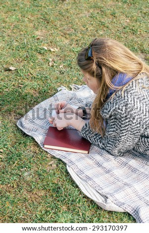 Girl studying and taking notes in a park, lying on the grass - stock photo