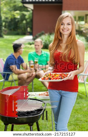 Girl supporting grill on a garden party - stock photo