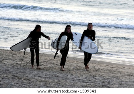girl surfurs walk on the beach with their boards after a long surfing day. - stock photo