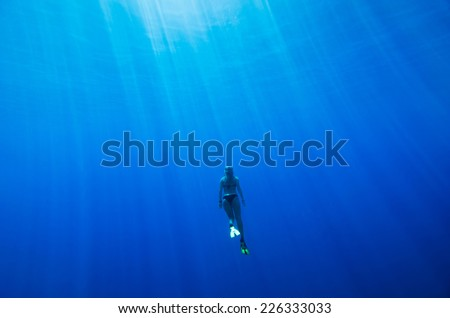 girl swimming underwater in a deep blue tropical sea - stock photo