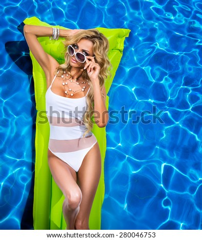 Girl swims in the pool on a green inflatable mattress - stock photo