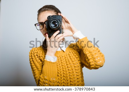 girl takes a photo of the old camera, hipster glasses isolated on a gray background - stock photo
