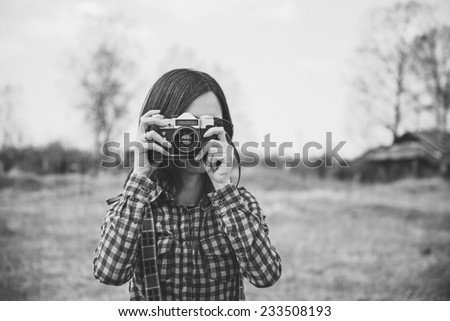 Girl takes photographs with vintage photo camera outdoor. With film grain and low contrast effect. Black-white photo. - stock photo