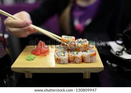 Girl takes sushi in the japanese restaurant - stock photo