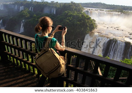 girl taking a photo of Iguassu waterfall with smartphone - stock photo