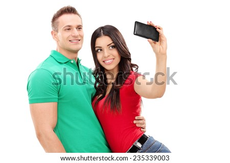 Girl taking a selfie with her boyfriend with a cell phone isolated on white background - stock photo