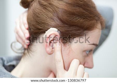 girl taking hearing aid - stock photo