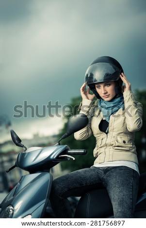 Girl taking on/Off her helmet - stock photo