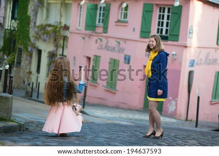 Girl taking photo of her friend in Paris - stock photo