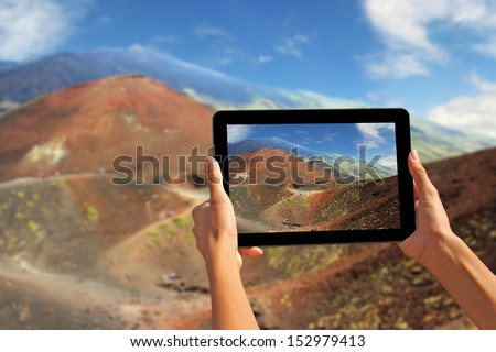 Girl taking pictures on a tablet, Etna volcano, Sicily - stock photo