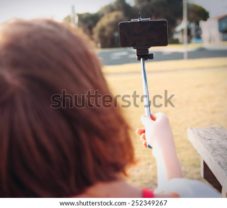 girl taking selfie picture outdoors,Focus on phone - stock photo