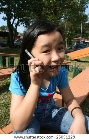 Girl talking on mobile phone in the park - stock photo