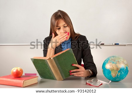 Girl teacher reading book and yawn - stock photo