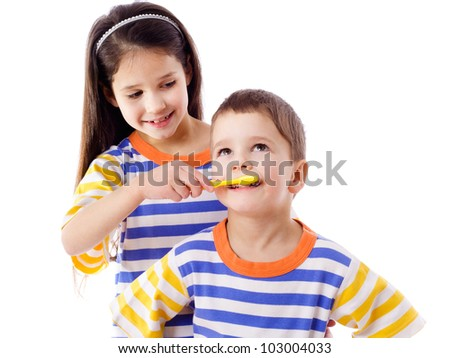 Girl teaches a boy to brush your teeth, isolated on white - stock photo