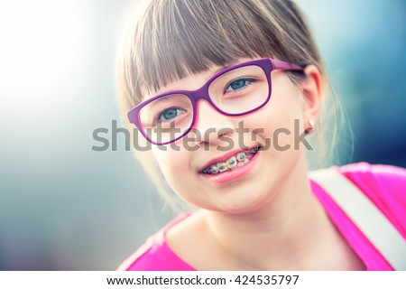 Girl. Teen. Pre teen. Girl with glasses. Girl with teeth braces. Young cute caucasian blond girl wearing teeth braces and glasses. Portrait of a smiling young girl. - stock photo